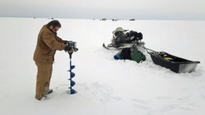 An angler makes a hole with an ice auger in preparation for fishing on Black Bay in northwestern Ontario. (Adam Young)