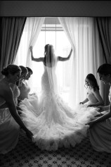 Bridesmaids arrange the train of a beautiful bride