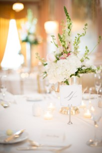 A table card and floral centerpiece for a sit-down dinner wedding reception