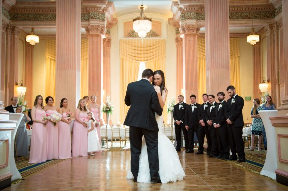 A bride and groom's first dance with bridal party watching