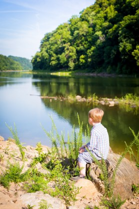A little boy watches the river