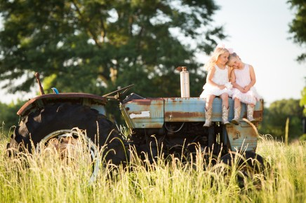 Twin sisters sit on an antique tractor