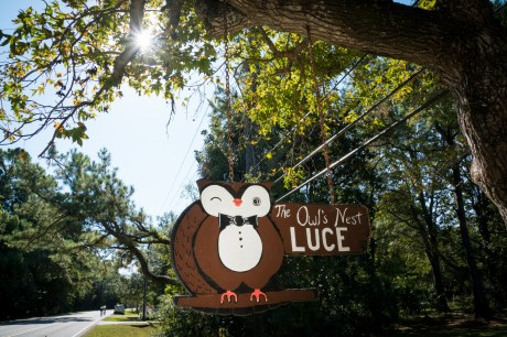 An rustic, hand-painted sign of an owl