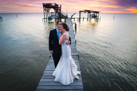 Bride and groom embrace at sunset