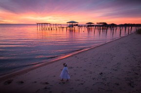 A little girl approaches water's edge at sunset