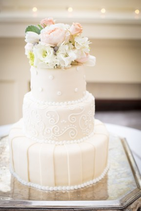 A three-tier wedding cake topped with fresh flowers