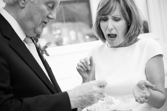 A bride reacts as the groom feeds her cake