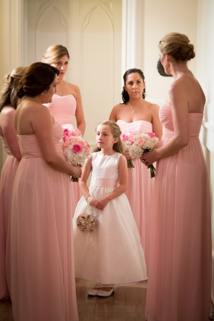 A flower girl surrounded by bridesmaids