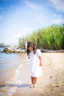A young girl in a white dress at the beach.