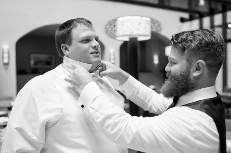 A groomsman helps the groom tie a bowtie