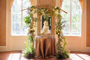 A four-tiered wedding cake under an arbor of fresh-cut flowers
