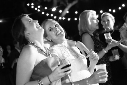A bride and bridesmaid laugh together