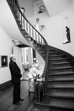 A father of the bride sees his daughter walk down a cantilevered staircase for the first time on her wedding day at the Bragg-Mitchell Mansion