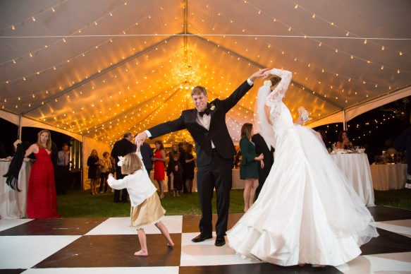The groom twirls the bride and a flower girl on the dance floor during the reception at the Bragg-Mitchell Mansion