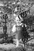 A blonde toddler holds onto a historic wrought iron bannister to steady herself coming down the front steps