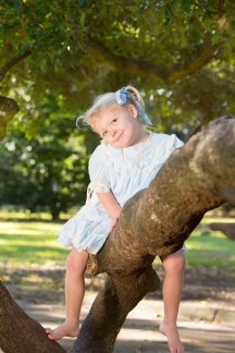 Blonde girl sits on a tree branch