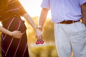 Pregnant couple holds University of Alabama Crimson Tide baby shoes