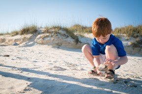 Red-headed boy finds seashells at the beach