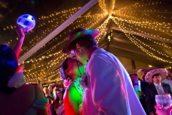 A kiss under the lights of the tent at Blackwater Farms