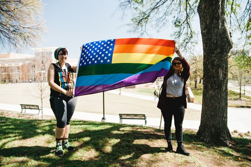 2 women holding a rainbow flag