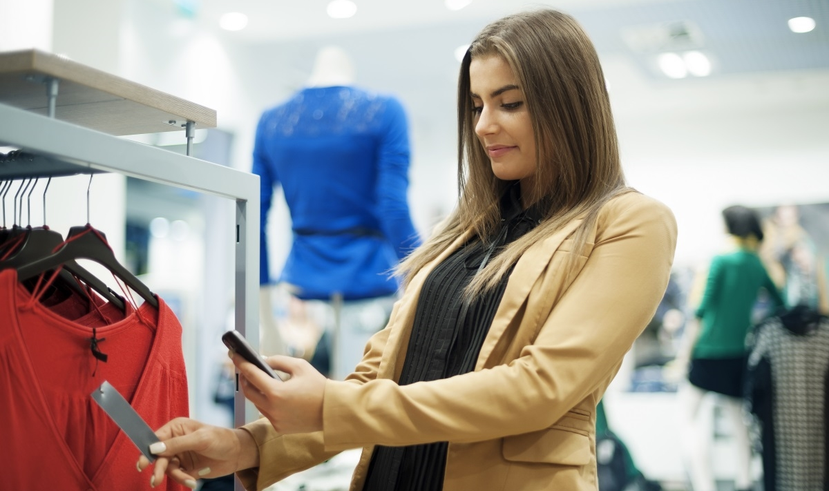 Happy woman using mobile while clothes shopping