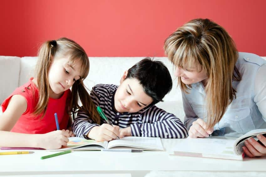 A little boy and two little girls kneeling at coffee table doing homeschool homework with a white couch and red wall background.