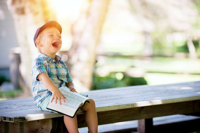 Little boy sitting on park bench laughing.