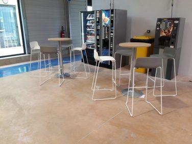 """2 espaces """"Café"""" équipés de manges-debout (dessus chêne clair et pieds tulipe gris alu) avec des tabourets Gelati blancs et gris"""