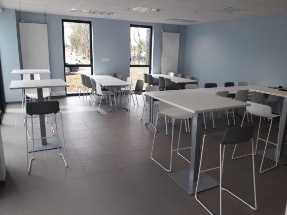 Réfectoire composé de tables basses et hautes avec des sièges/tabourets Gelati gris et blancs
