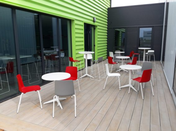 Espace réfectoire extérieur avec une alternance de tables hautes et basses Outdoor et de sièges Gelati en coloris blancs, gris et rouges
