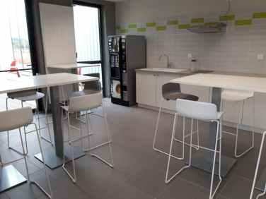 2 ème réfectoire composé de tables hautes avec des tabourets Gelati gris et blancs