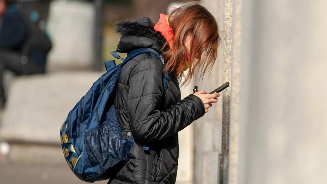 Dziewczyna z telefonem w ręku i plecakiem na plecach