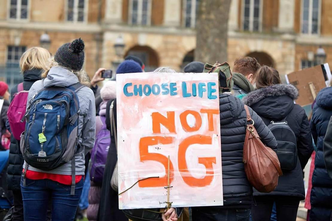 """Ludzie protestujący przeciwko 5G z transparentem """"Choose life – no 5G"""""""