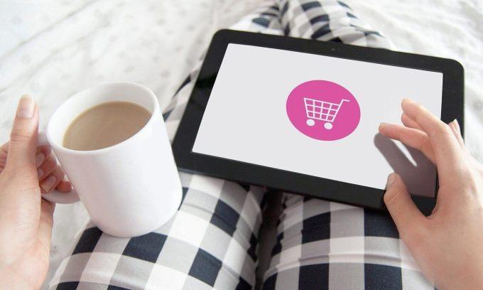 Zakupy online (tablet na kolanach, kubek z kawą w ręku)