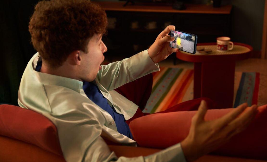 Mężczyzna siedzący na kanapie i trzymający smartfona OPPO A53