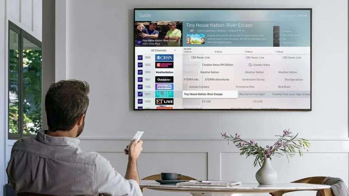 Mężczyzna przełączający kanały w usłudze Samsung TV Plus na Smart TV