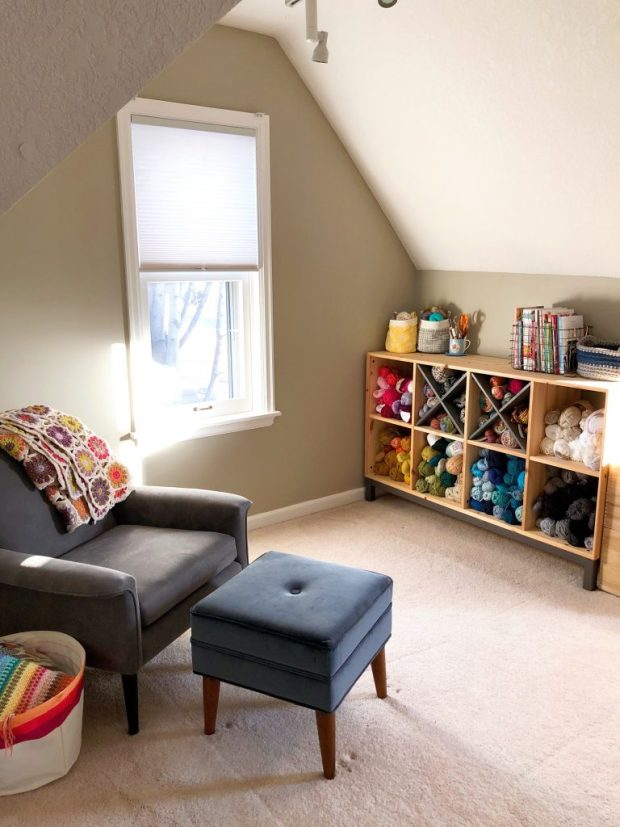 Bedroom nook with a shelf of yarn and comfortable chair