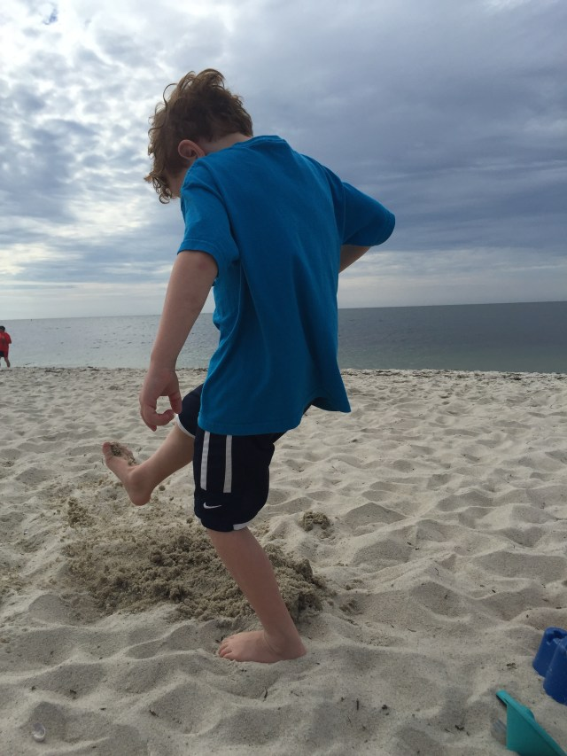 Boys kick sand