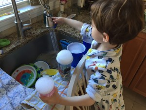 Playing with soap and water and cups at the kitchen sink