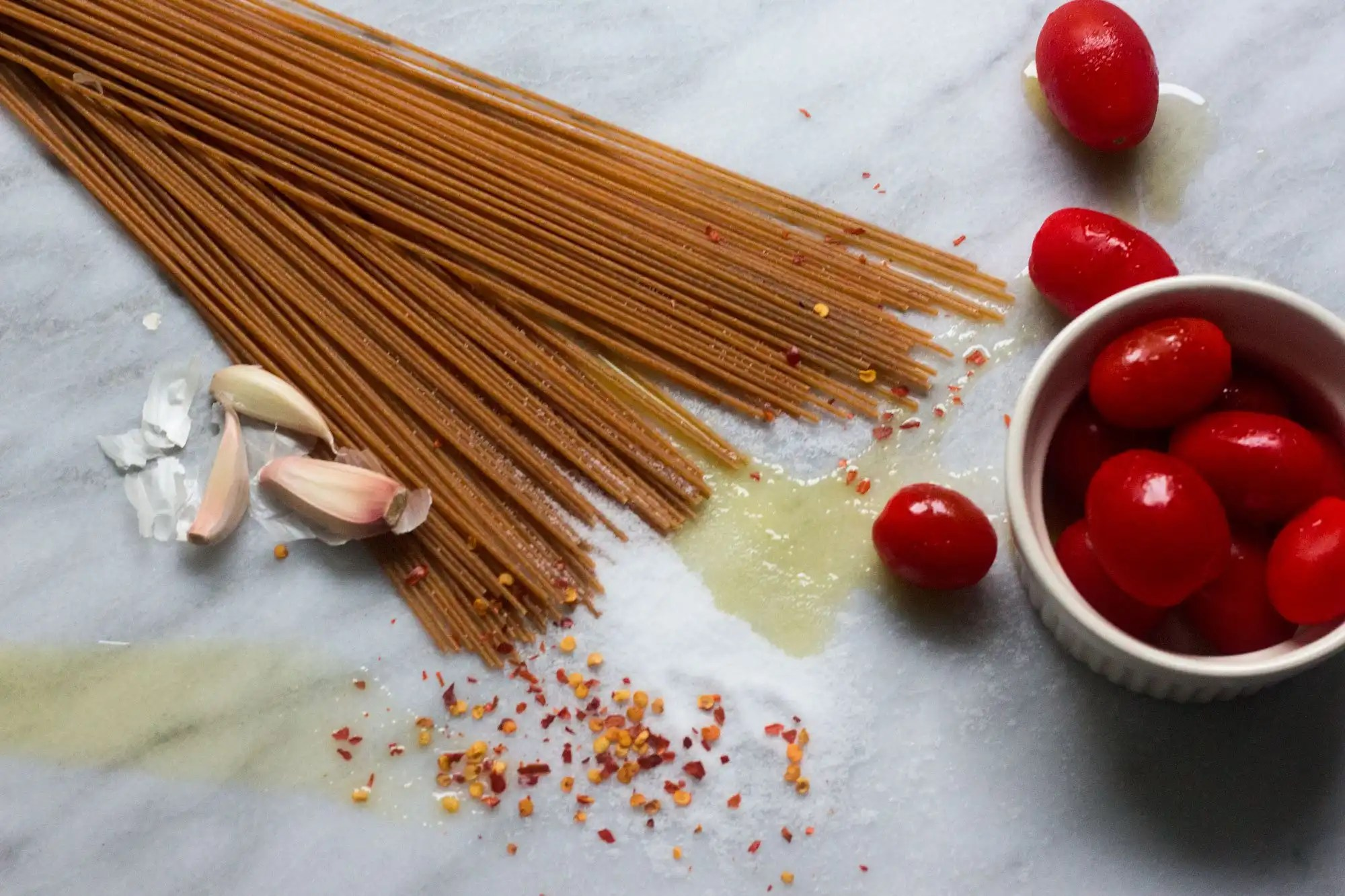 raw ingredients for whole wheat spaghetti with garlic blistered tomatoes