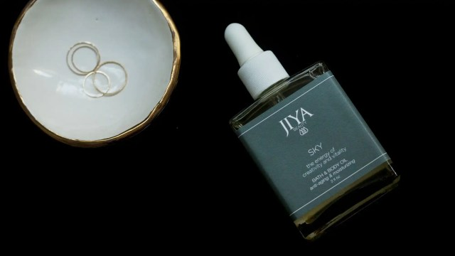 Bottle of Jiya Beauty Sky Body Oil on black background adjacent to a bowl of rings.
