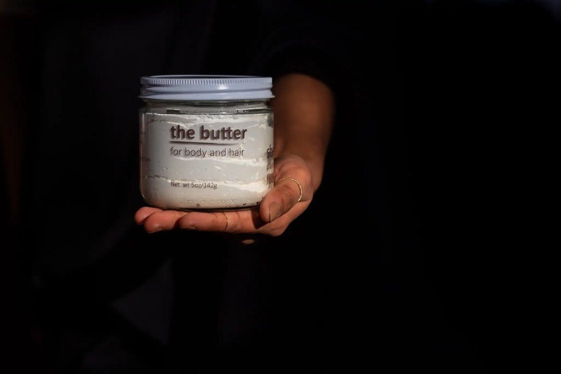 she plants love the butter held in hand on a dark background