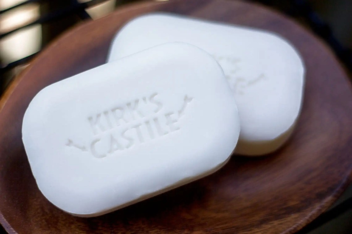 two white bars of kirk's castile soap on a wood plate