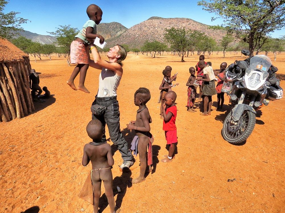 Almudena Teulón con varios niños africanos al dar la vuelta al mundo en moto
