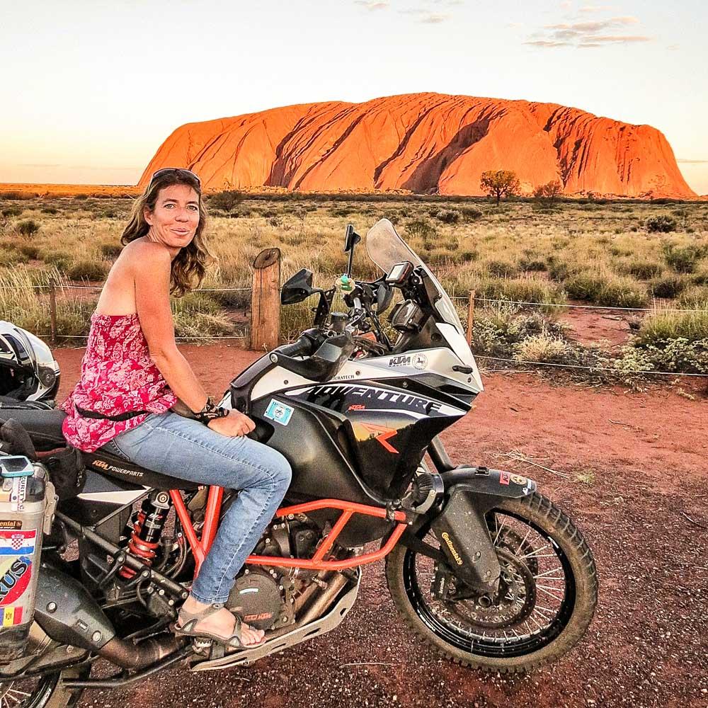 Almudena Teulón junto con su moto en el Monte Uluru, Australia