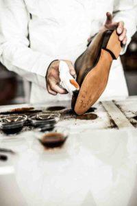 Un artigiano applica la patina su una calzatura a marchio Berluti