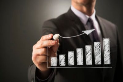Business person drawing ascending bar chart graph