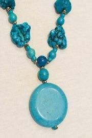Detalle medallón del collar de piedra natural.