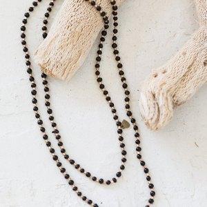 Collar que recuerda al rosario, color negro.
