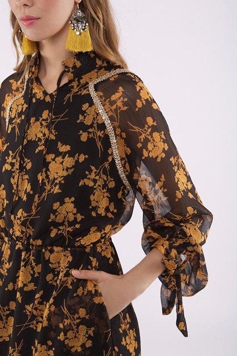 Detalle de la fornitura del hombro y estilo de manga del vestido floral canela sobre fondo negro.